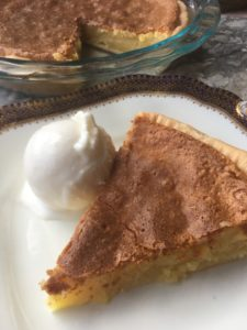 One slice of Almond Custard Pie with ice ream on a plate