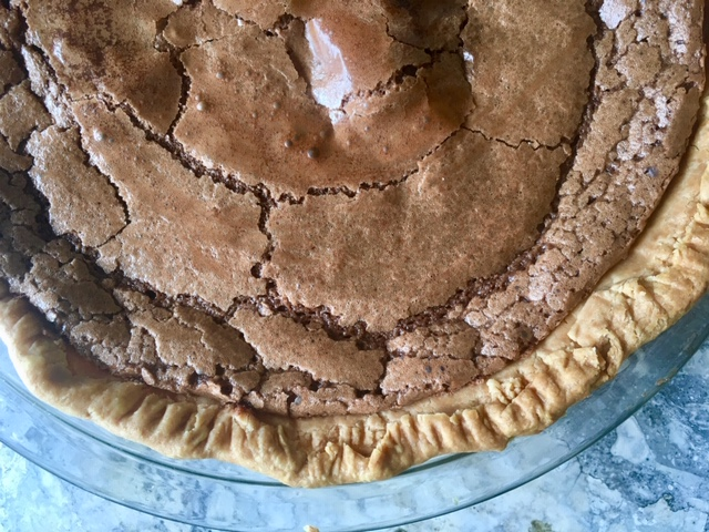Crackly, chocolatey pie with rustic fork-pressed pastry crust in glass pie pan on marble surface