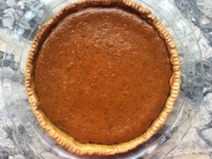 Big delicious pumpkin pie, in a glass pie pan on a marble countertop, viewed from above