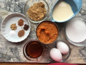 All the ingredients for delicious pumpkin pie, arranged in bowls on a marble board