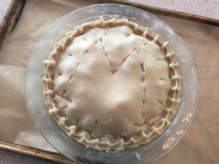 """Before picture of muscadine grape hull pie, filled, crimped edges, vents poked in top with letter """"M"""" as centerpiece. on parchment and wooden surface in glass pie plate"""