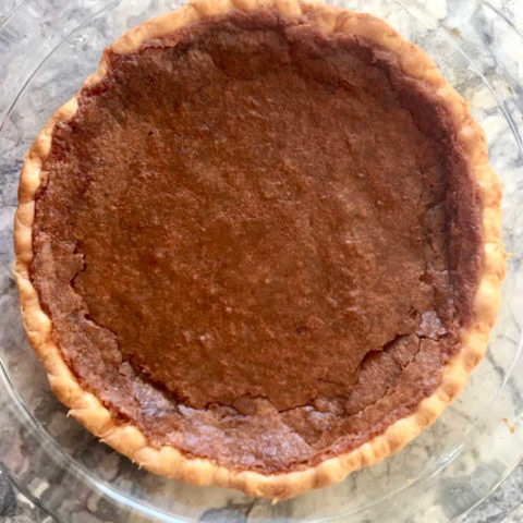 Classic Chess Pie, whole in glass pie pan on marble surface, handsome deep brown crackly surface