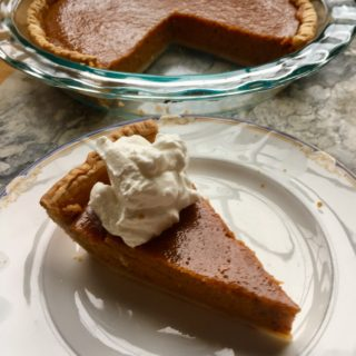 One piece of pumpkin pie on a china plate, with remaining pie in background, in heatproof glass pie plagte