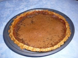 Chess pie in a metal pie, uncut, lighter golden brown