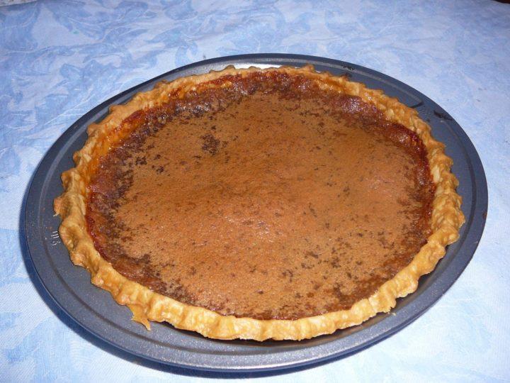 Chess pie in a metal pie, uncut, lighter golden brown