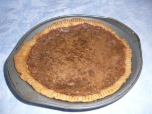 Classic Chess Pie in a metal pie pan, from above and back on a blue tablecloth