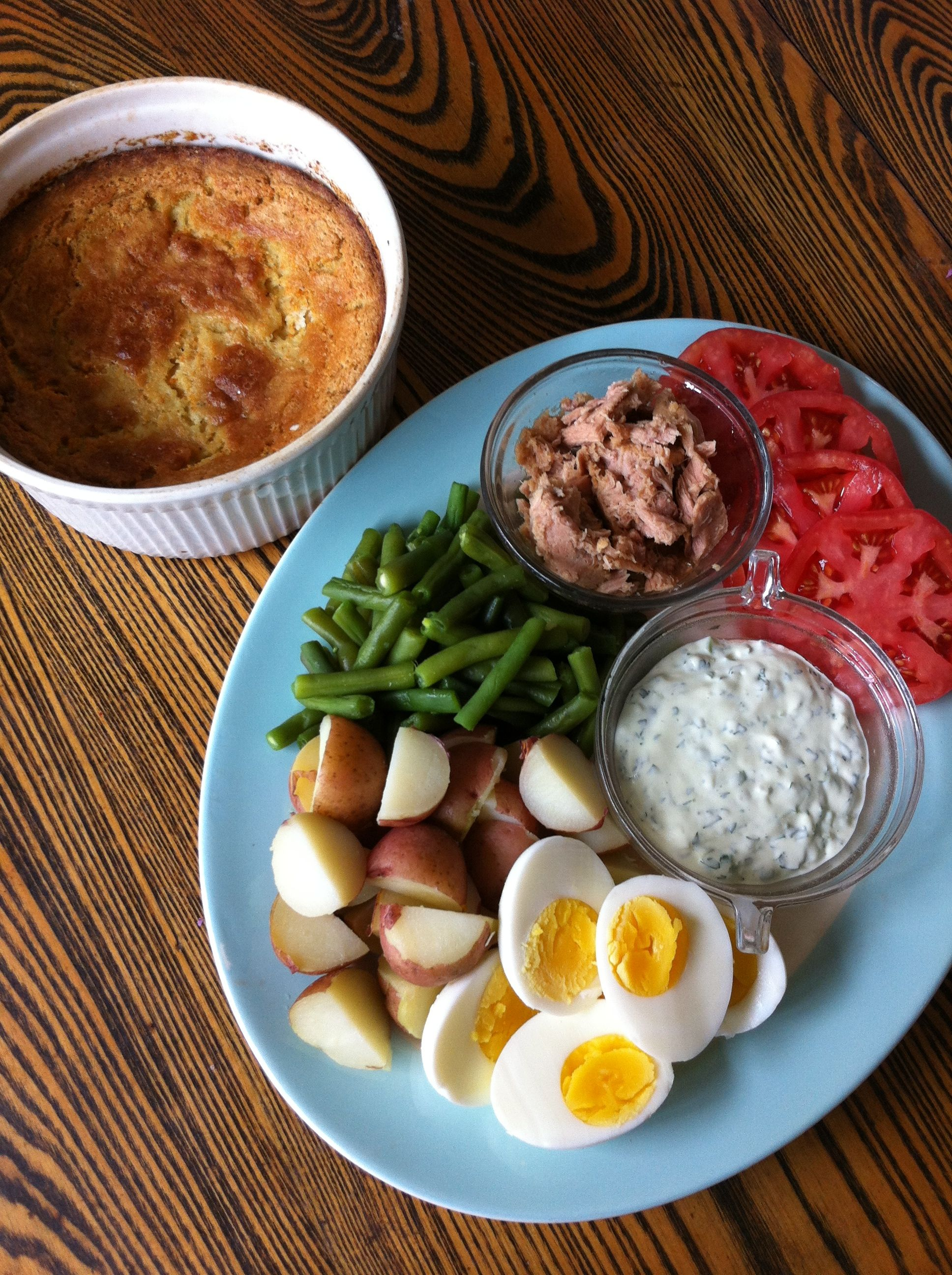 Big baby blue platter with simple Nicoise-style salad of potatoes, green berans, sliced tomatoes, hardboiled eggs, tuna, and herb mayonnaise, with a big beautiful casserole of spoonbread on the side