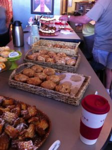 Good things to eat lined up on the counter at WPA bakery in Richmond VA: Pans of doughnuts and danishes and more with a to go coffee front right