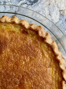 Close up of the surface of a freshly baked Tyler pie, with crimped crust in glass pie pan on marble surface. Golden brown and delicious-looking!