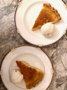 Twin Tyler pie pieces, from above, on elegant china dessert plates, with ice cream, on a marble countertop