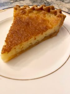 One piece of golden yellow Tyler pie from the side, on a white china plate with bumpy carmaelized surface and creamy filling, pointing toward the viewer in a tempting fashion..