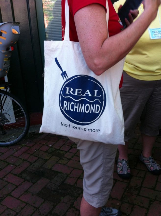 Close up of a white canvas tote bag with the Real Richmond Food Tours logo on the shoulder of a tour-member . Close up of the full bag with skillet logo