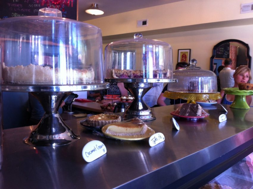 View of baked goods on the counter at WPA Bakery with one piece of Tyler Pie in the center and windows and shop in the background