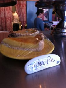 Tyler Pie on the counter at WPA Bakery in Richmond VA, with a ceramic sign IDing it and workers in the background