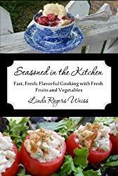 Cover of Seasoned in the Kitchen, a cookbook, with beautiful berries in a blue bowl on top, crab stuffed tomatoes on the bottom, and title and author in the middle.