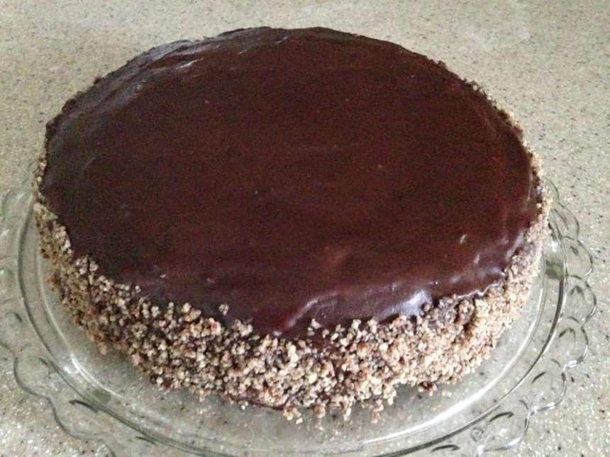 One layer chocolate torte, enrobed in luscious chocolate ganache, with chopped pecans covering the sides.