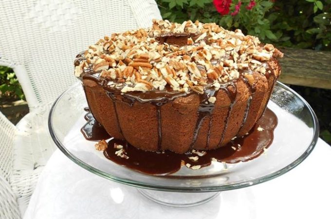 Chocolate pound cake on a glass cake stand, with chocolate glaze on top, covered with chopped pecans, on a white tablecloth outdoors, with red flowered bushes in the background