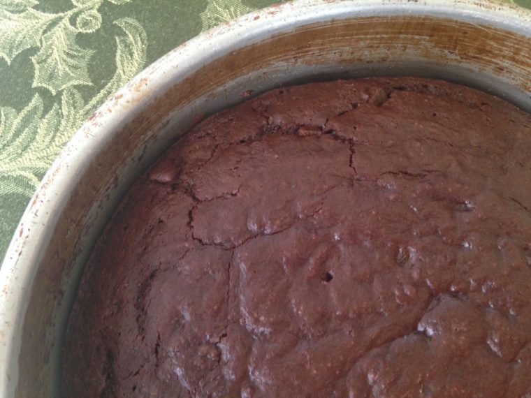 Close up of 15 minute chocolate cake still in the cake pan, top 1/4rh view, metal pan on a green tablecloth
