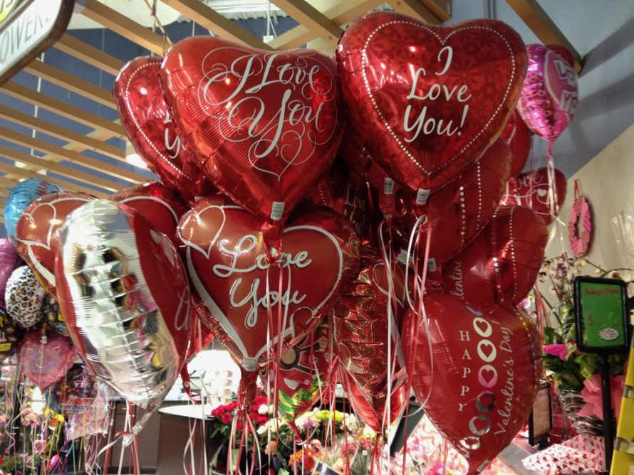 Dozens of Valentine's Day balloons, floating in a display (anchored of course) in a grocery store, with ribbons hanging down and sweet messages of love in golden glitter