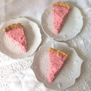 Three pieces of strawberry icebox pie on white plates with stylish dots on white lacy tablecloth