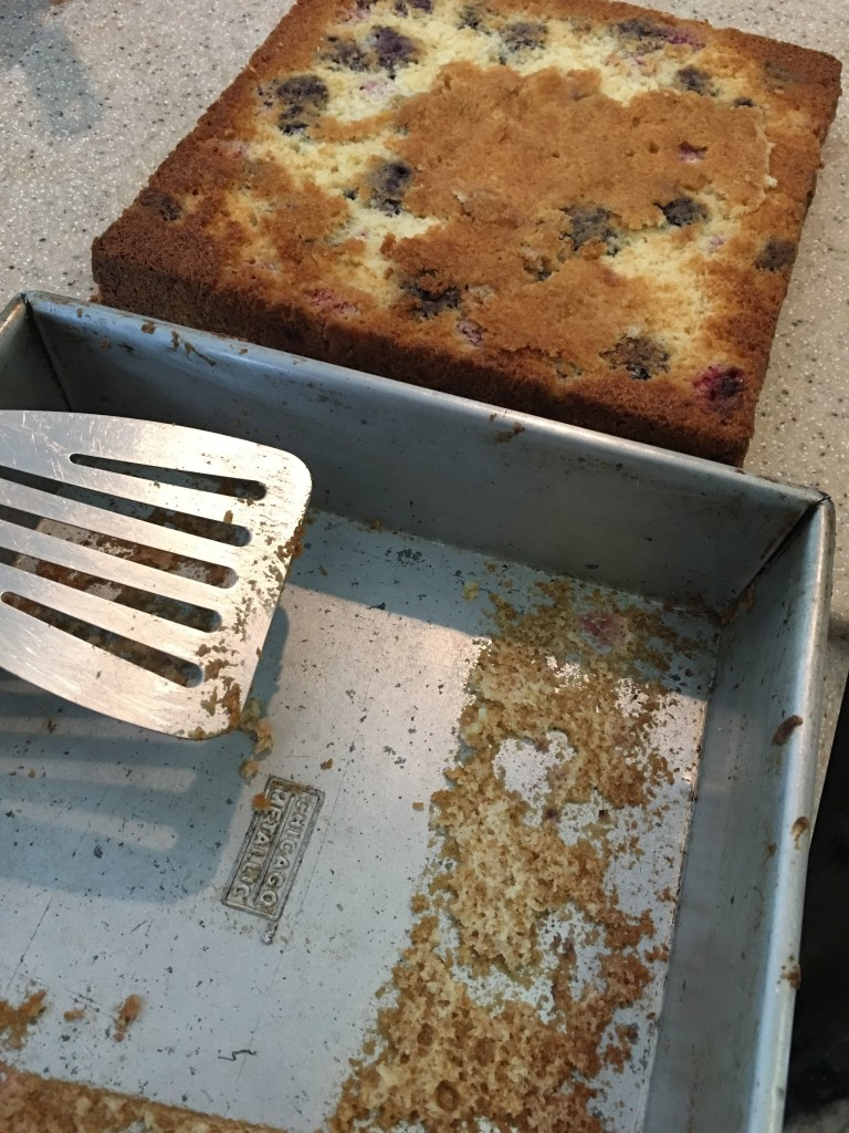 Nine-inch square blueberry cake sits cooling on a cutting board in the background, while foreground shows cake pan and spatula from which cake was just removed. Some yummy crumbs remain in the pan. Next time more butter! This time, scrape them out and add to the layer, which has some blueberries showing in patches where some cake stuck to the pan.