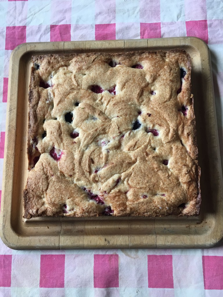 Blueberry cake, turned out of its pan and placed right side up on square wooden cutting board for a cool-down