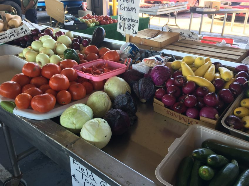 Produce on display at the NC State Farmers Market, with muscadines in the front right corner and all kinds of goodness in the vicinity