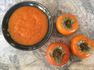A black bowl full of bright orange persimmon puree, with three fuyu persimmons to the right all on a marble countertop
