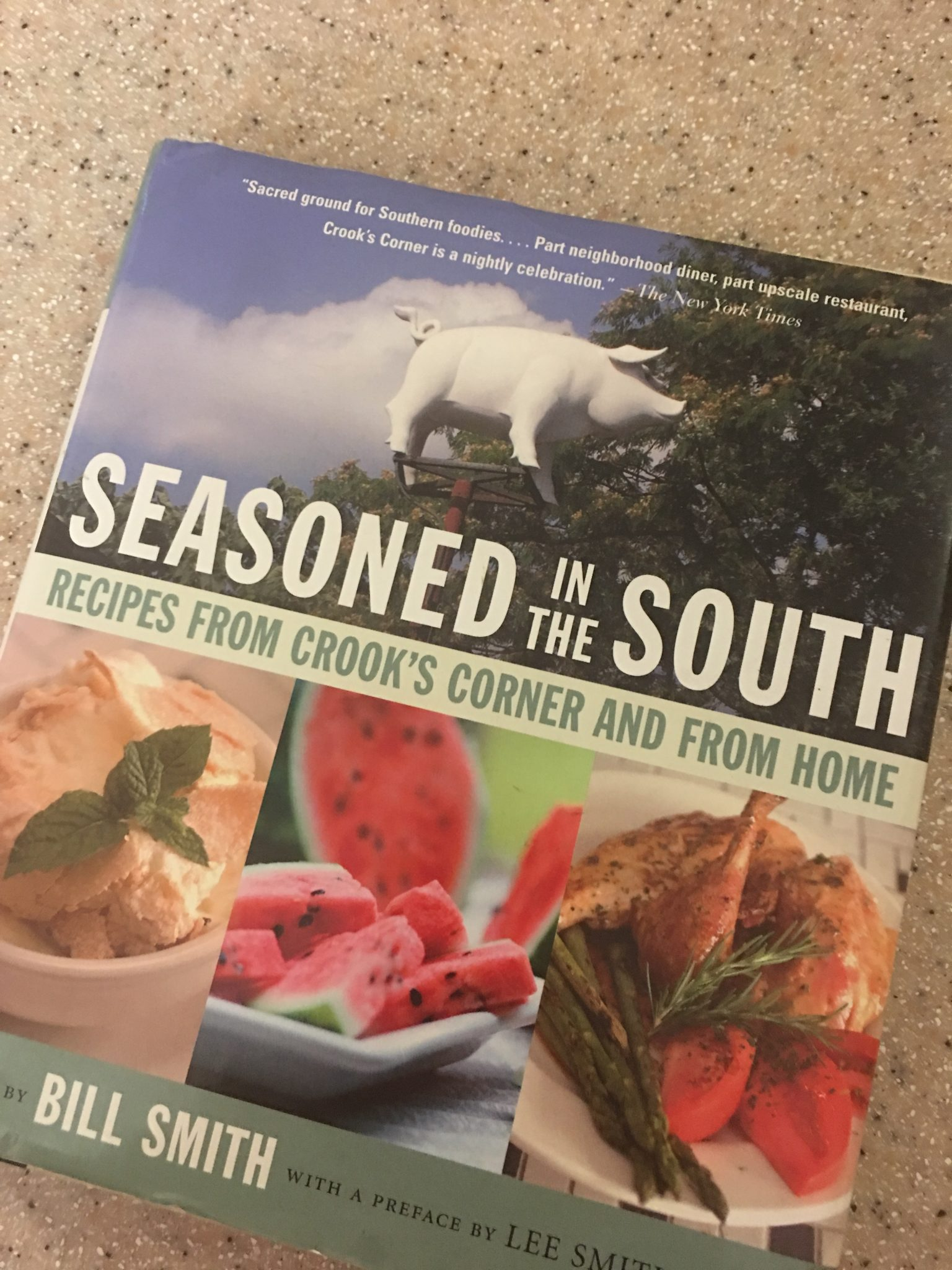Cover of Bill Smith's first cookbook, Seasoned in the South, on a speckled countertop, showing the giant pig on display on the roof of Crook's corner, and a few dishes on the cover, including Bill's Good Banana Pudding with mint sprig and cold fried chicken with watermelon slices on the side