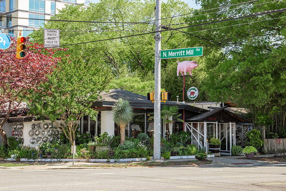 Crook's Corner viewed from across the street, at the intersection of East Franklin Street and Merrit Mill Road with spring green trees above and wonderful local flowering plants around the entryway