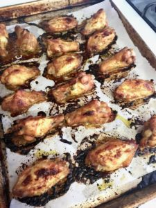 Wings on a sheet pan, with parchment paper lining to catch the juices and make clean up easy.