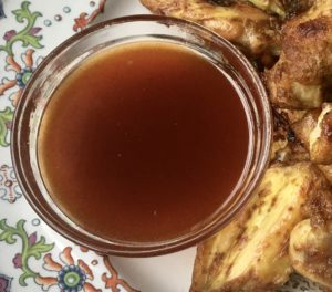 Sweet and Hot Dipping Sauce in a Small Glass Bowl, seen from above. Wings on the right.
