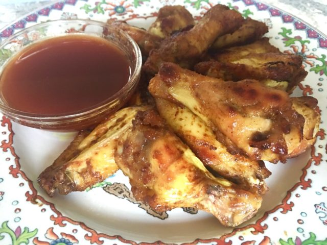 Close up view of Honey-Mustard Chicken Wings, piled on a pretty white plate with flowery rim and a small glass bowl of dipping sauce in top left corner.