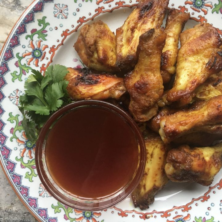 Chicken wings with honey-mustard flavor and sweet-hot dipping sauce, piled on a colorful plate on marble countertop