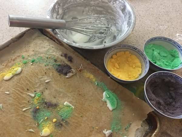 Clean-up time! The half-sheet pan still covered with baking parchment and big drips and blobs of icing and piles and dustings of colored sugars. This is where the icing phase took place, Top of the frame shows empty icing bowl with whisk at rest; to its right, the three bowls with plenty of gold, green and purple decorative sugars, ready to be poured in jars and set aside for decorating my next Mardi Gras cake.