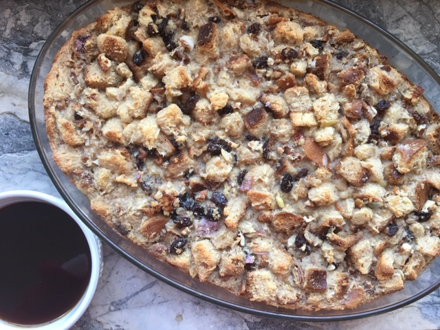 Big oval bread pudding with raisins and pecans and a side of bourbon sauce