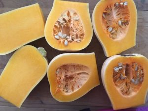 Butternut squash, cut open in quarters, with seeds in and peel on, viewed from above