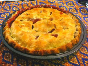 "A handsome double-crust sour cherry pie, with ""C"" cut into pastry to make vents, baked in metal pie plate, displayed on blue patterned tablecloth"