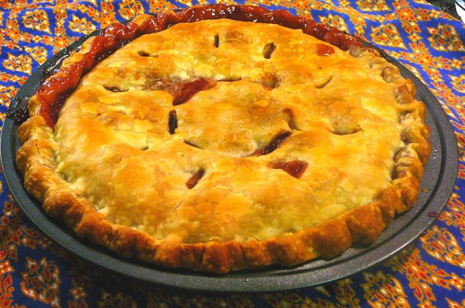 """A handsome double-crust sour cherry pie, with """"C"""" cut into pastry to make vents, baked in metal pie plate, displayed on blue patterned tablecloth"""