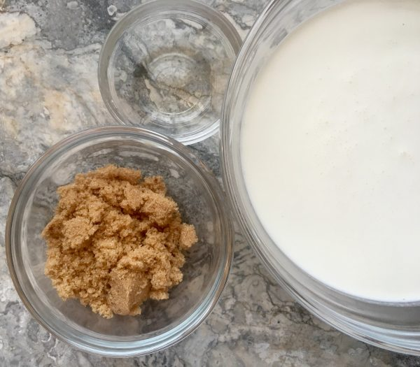 The ingredients for making whipped cream in three glass bowls on a marble countertop, with light brown sugar bottom left, big bowl of creanm filling right half, and small bowl of clear almond extract at top, a trio of prep for a finishing flourish.
