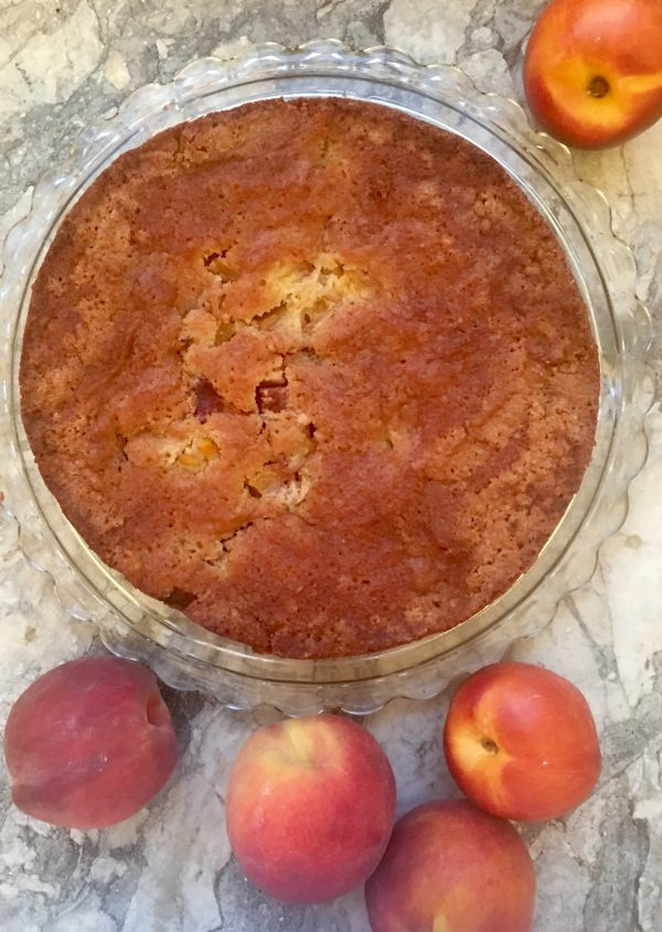 Looking down on a peach and nectarine torte, on a glass serving plate on a white marble surface, with 2 peaches and 3 nectarines around it (and chopped up inside it)