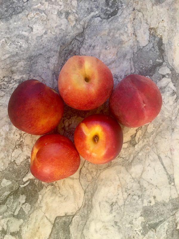 3 nectarines and 2 peaches on a marble countertop, so colorful and lovely