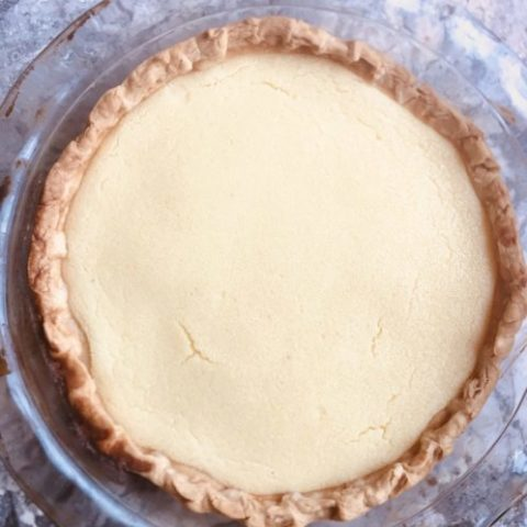 Buttermilk pie in pastry crust, glass pie plate on marble counter