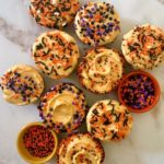 Nine gorgeous pumpkin cupcakes with pumpkin icing and spooky sprinkles on marble counter with small bowls of trick-or-treat sprinkles