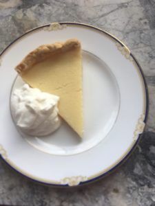 One slice Easy Buttermilk Pie on Round plate gold and navy blue trim on marble counter top. Whipped cream garnish!