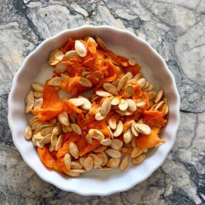 Small white shallow ramekin holding pumpkin seeds, orange and white, on marble countertop