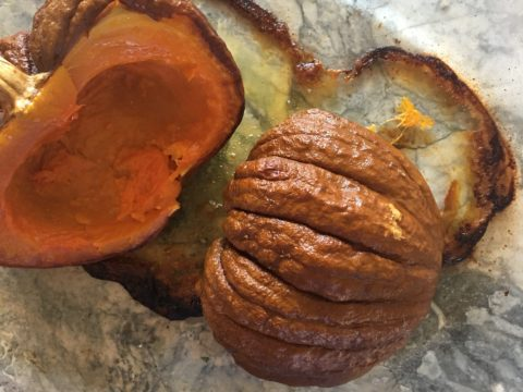 Halved pumpkin, seeded, halved, and roasted, ready to be scraped out of its thin skin, and mashed into puree.