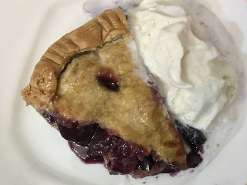 one piece of muscadine grape hull pie wiht whipped cream on white plate with juicy purple filling showing