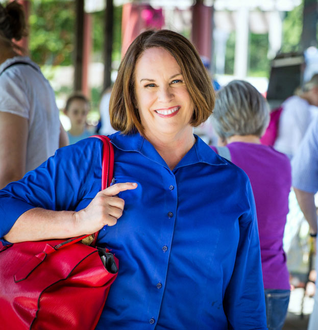 Nancie McDermott in royal blue collared shirt with sleeves rolled jup, big red bag over one shoulder smiling at camera with farmers' market scene in background