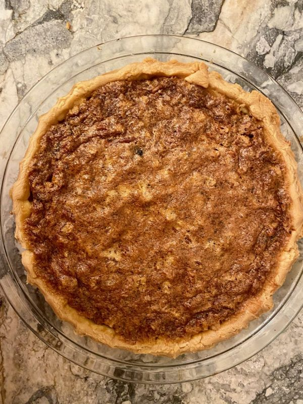 top down view of Osgood Pie, a chess pie with raisins and pecans, pastry crust, glass pie pan on marble counter